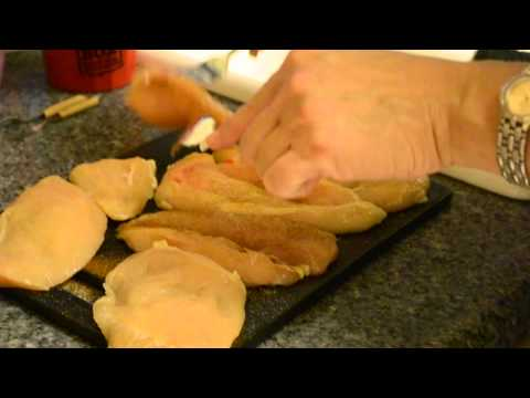 Mom seasoning and tenderizing chicken