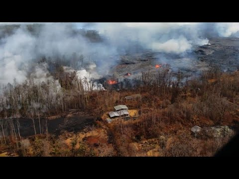 Aerial images of lava surrounding homes in Hawaii