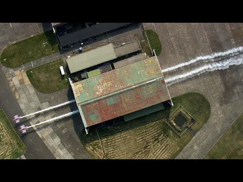 Two Planes Fly Through a Hangar – Red Bull Barnstorming