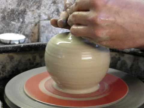 Attempting to make a pottery  Apple shaped clay pot on the potters wheel throwing demo