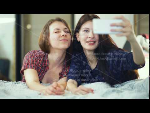 Two happy women friends lying in bed and making selfie in morning and have fun on bed