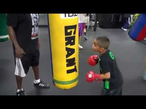 Jeff Mayweather instructing a little kid on the heavy bag