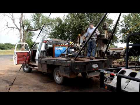 Raising the poles on a small winch truck.