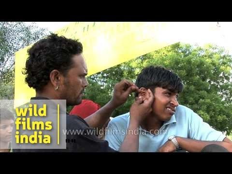 Street-side ear cleaner makes client scowl, in Delhi