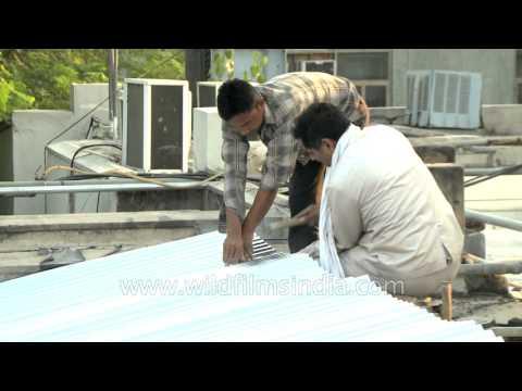 Indian men laying GI sheets to make roof