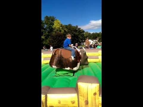 Brother riding a fake bull