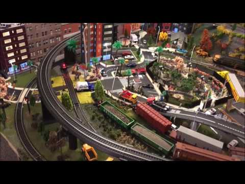 HO model train layout with mountain, city and bridges