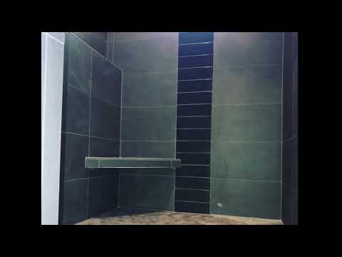 Charcoal large format tile shower with glass accent and hexagon floor complete