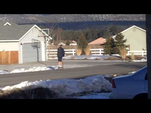 Big kid wearing shorts in the snow and riding a little scooter