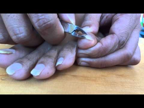 Guy is cutting his toenails