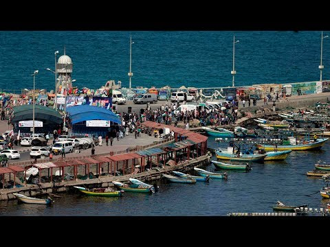People gather at the Gaza port to see a cruise set off