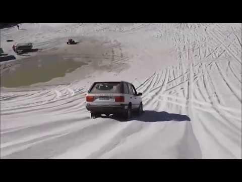 Girl driving Range Rover in sand dunes