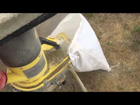 Grinding corn with a wood chipper.