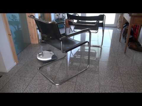 Vorwerk Kobold VR100 tries to climb tubular chrome chairs , Bauhaus style