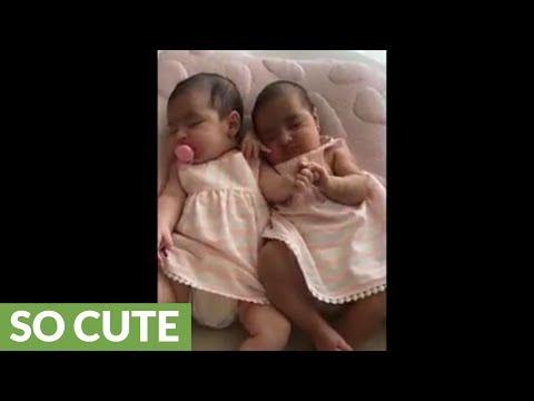 Precious twins hold hands while they sleep