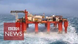 Huge waves crash against swaying North Sea oil rig
