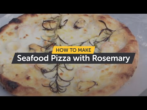 Making a seafood pizza with rosemary