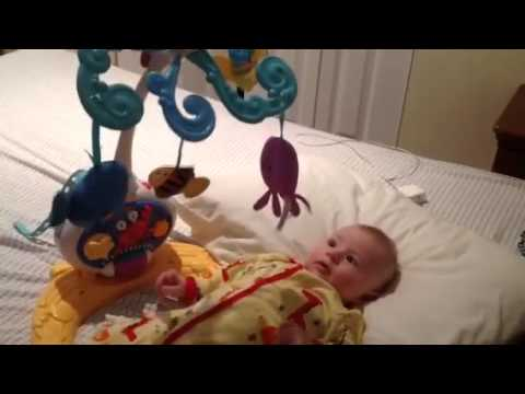 Baby playing with crib mobile