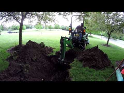 Compact Tractor Backhoe Digs Sewer Clean-Out