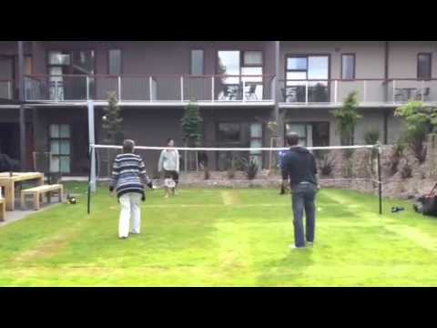 Playing badminton on a grass court