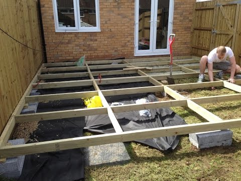 Installing a basic raised frame decking, with reclaimed scaffold boards over a sloped lawn.