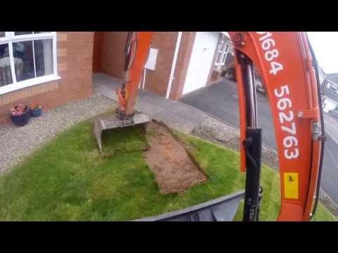 Mini Digger Removing Turf From A Lawn