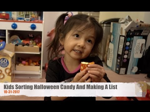 Kids Sorting Halloween Candy And Making A List