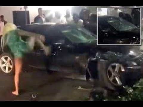 Barefoot angry woman smashes car window with karate kick
