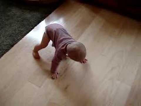 baby on wood floor crawls on toes