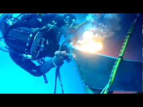 Commercial Diver burning off damaged steel plate underwater using