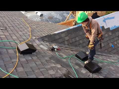 Plumbers cut holes in new shingles