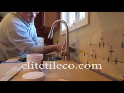 Time lapse Travertine subway tile backsplash with a mosaic glass tile border