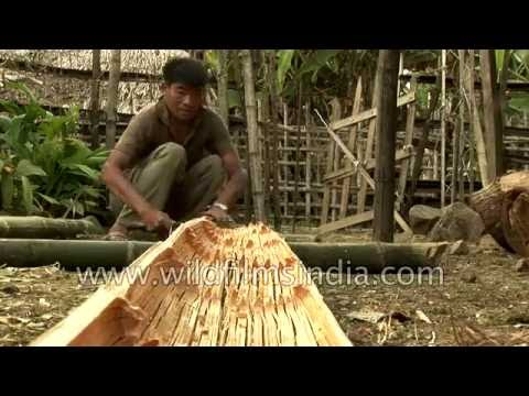 Arunachali man chisels bamboo poles to make a hut in Upper Siang