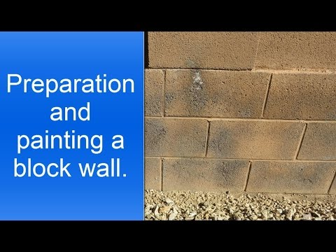 Spray painting a cinder block wall.