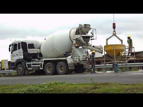 CEMENT MIXER TRUCK WORKING POURING MIX INTO CRANE CONCRETE BUCKET