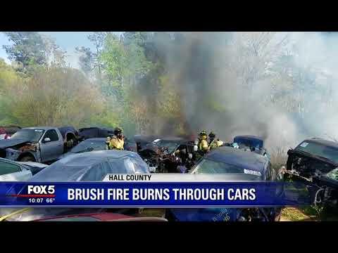Brush fire burns through cars