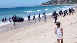 Sunbathers shocked as migrants storm Spanish beach