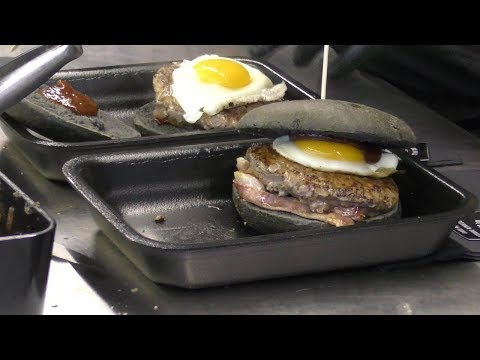 Master of BLACK BUN Burgers with Best Italian Meat, Eggs and Bacon. Street Food