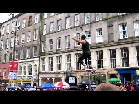 Fringe Festival performer juggling with knives on giant unicycle