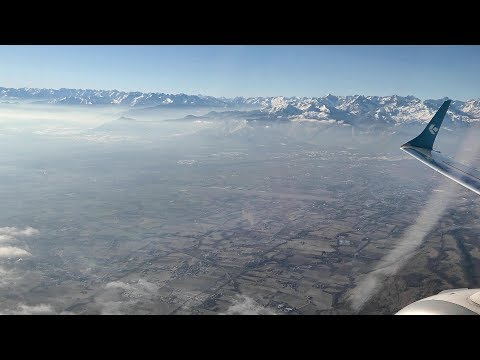 Takeoff from Turin Airport. Crossing of Snowy Mountain Italian Alps