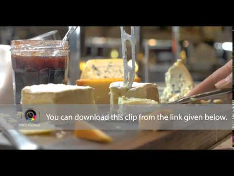 Hands Cutting Soft Cheese with Knife