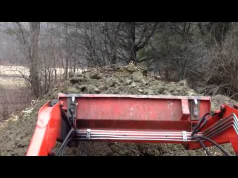 Adding clay to the horse manure compost pile.