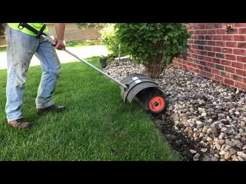 Power broom clears rock away from plastic edging.