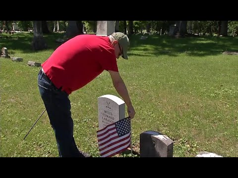 Volunteers place flags on graves of military veterans
