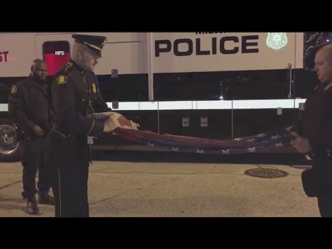 Officers ceremoniously fold flag burned by protester