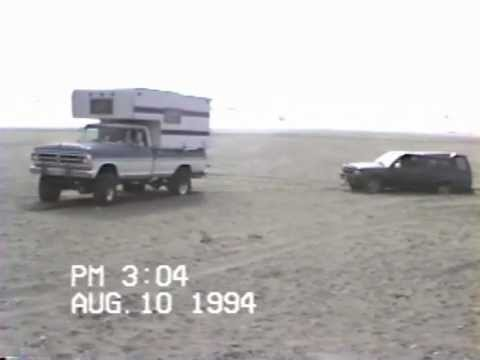 F250 Highboy pulling truck toyota out of sand