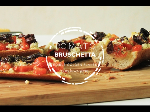 Tomato Bruschetta with feta cheese, sliced olives and olive oil with edible golden flakes