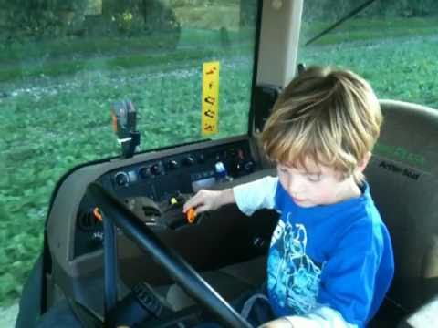 Farmer James driving John Deere tractor at harvest 2010