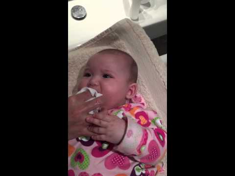 5 months infant getting mouth and face wash.MOV