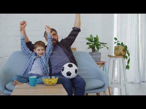 Family members father and son are watching soccer match on TV at home, cheering, celebrating victory